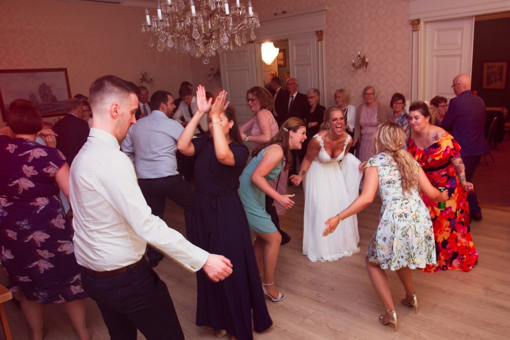 Brud og bryllupsgjester som danser masse.