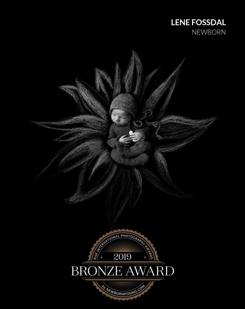 Liten baby i en tegnet blomst på svart bakgrunn. Fikk bronse i Rise Awards.