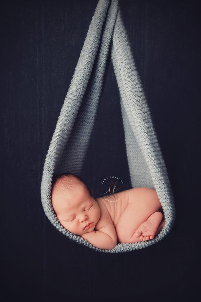 Et baby hengende i et pledd. Dette er ikke ekte, og baby ligger egentlig trygt på en beanbag.