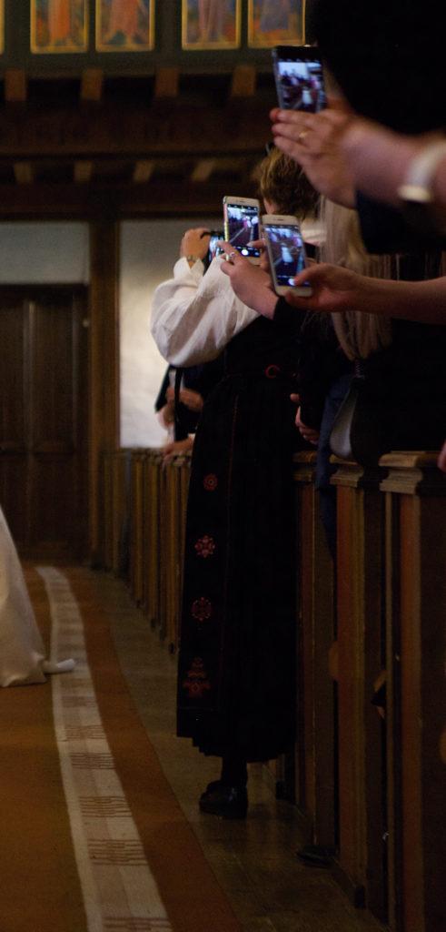Bilde av gjester i en kirke som står med mobilene sine. Dette er typisk for mobilbruk i bryllup.