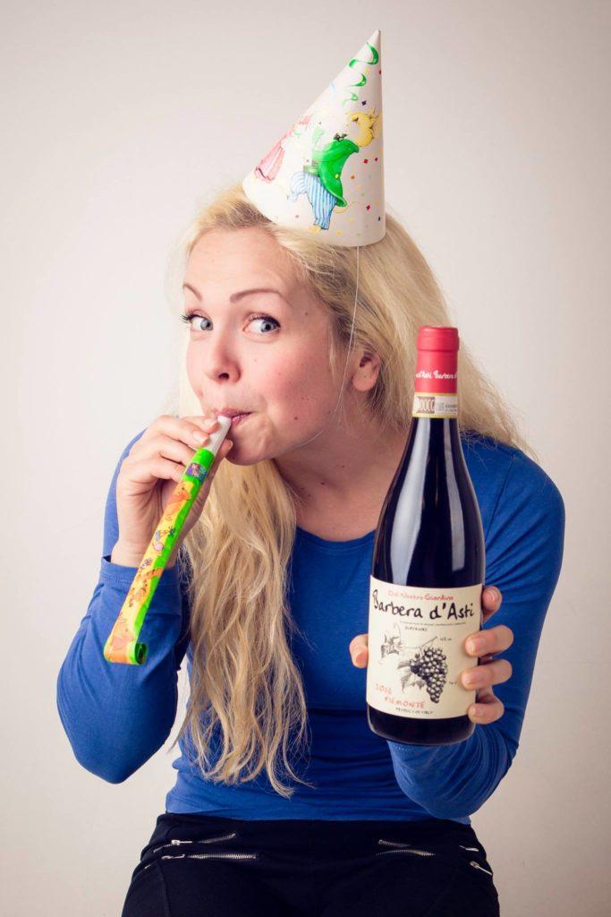Lene, fotografen. ser i kamera og smiler. Hun har vin i hånden og bursdagshatt på hodet. Hun feirer 10 års jubileum med eget firma.