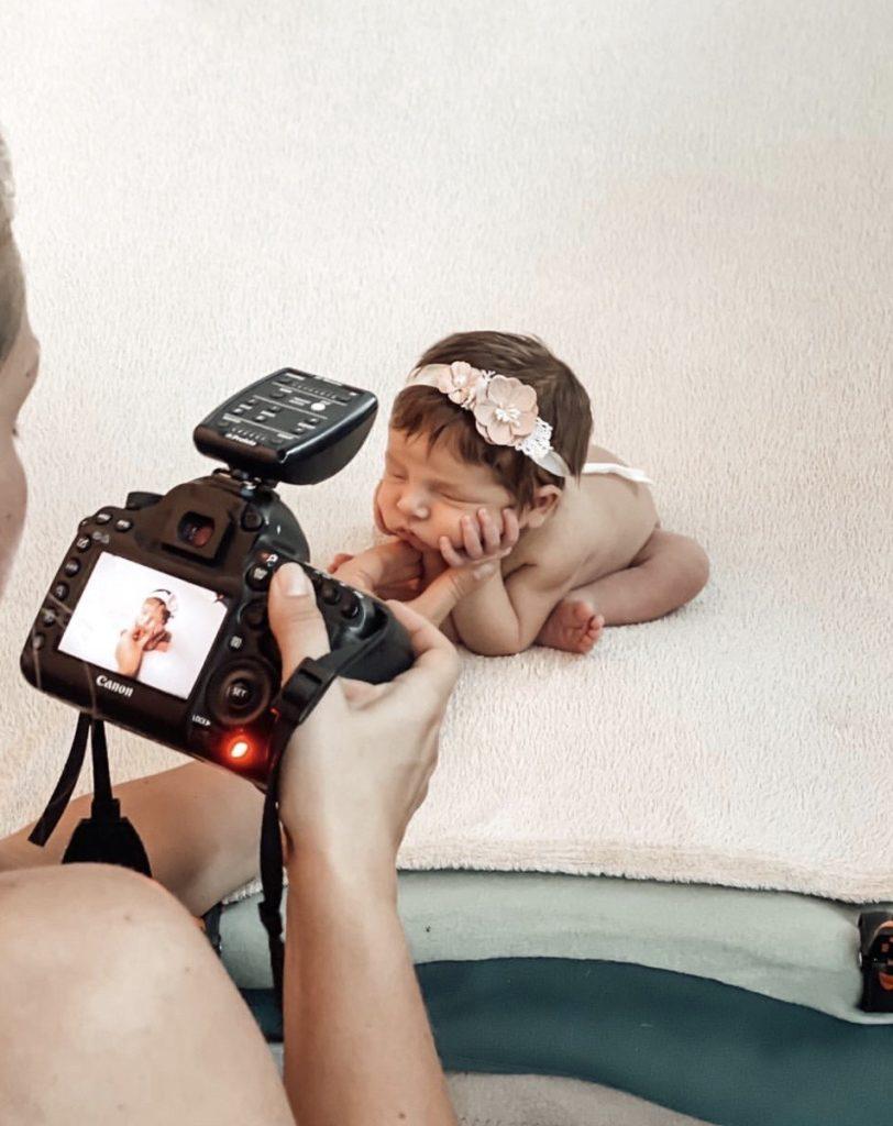 Behind the scenes bilde av Lene som fotografere en nyfødt.