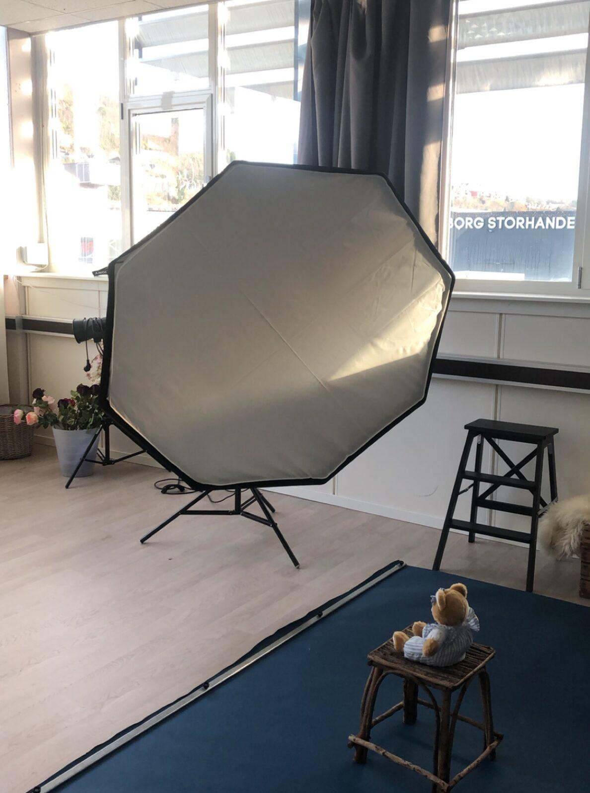Bilde av en blits og en bamse på et lerret. Viser et av rommene i nytt fotostudio i Åsane.